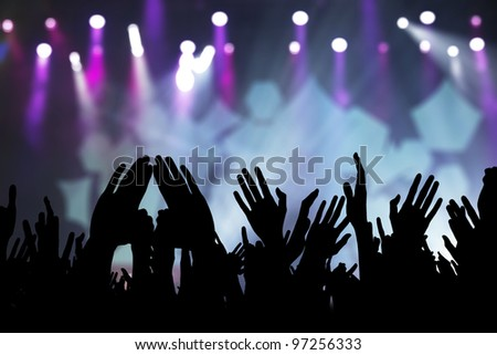 Photos of hands raised at rock concert, silhouetted against stage lighting. - stock photo