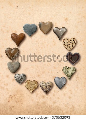 Photos of heart-shaped things made of stone, metal and wood, assembled into a circle over vintage paper background. - stock photo