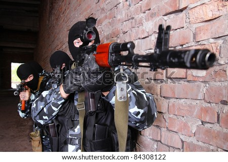 Photos of heavy equipped soldiers or terrorists in black masks with automatic guns. - stock photo