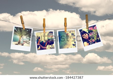 Photos of holiday hanging on clothesline by clothespins. Sky and cloud on background. - stock photo