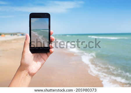 photoshooting on smartphone at sea coast - stock photo