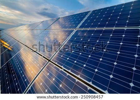 Photovoltaic cells on a background of a cloudy sky - stock photo
