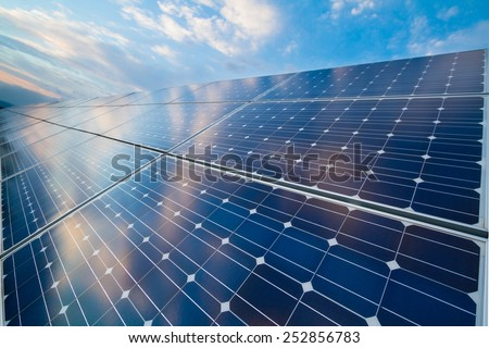 Photovoltaic cells with reflection of cloudy sky - stock photo