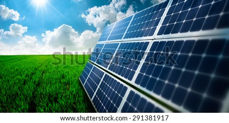 Photovoltaic ecological modules on green grass valley against of sun and cloudy sky - stock photo