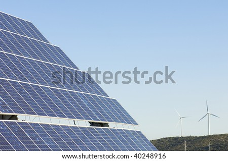 photovoltaic panels and windmills in a hill - stock photo