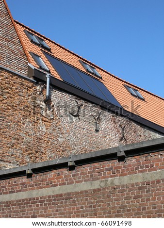 Photovoltaic panels integrated into historical roof - stock photo