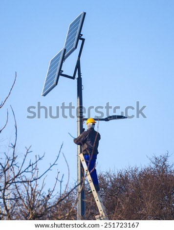 Photovoltaic panels renewable eco energy concept. Male engineer at work place, solar charging batteries on pole - stock photo