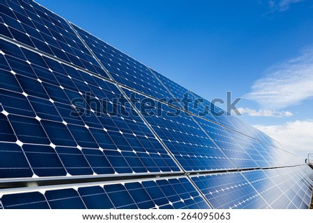 Photovoltaic solar panels and sky with few clouds - stock photo