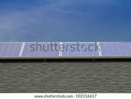 Photovoltaic Solar Panels Mounted on Roof with Blue Sky Background - stock photo