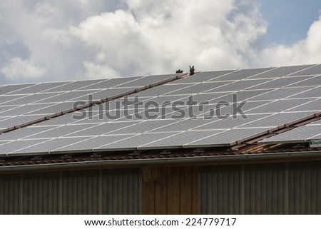 Photovoltaic solar panels on a roof for converting the solar energy of the suns radiant emissions to electricity in a sustainable alternative resource in an eco friendly power and energy concept - stock photo
