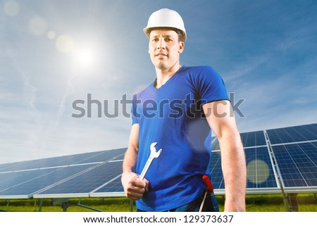 Photovoltaic system with solar panels for the production of renewable energy through solar energy, a technician or worker standing in front - stock photo