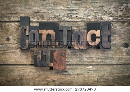 """phrase """"contact us"""" written with vintage letterpress printing blocks on rustic wood background - stock photo"""
