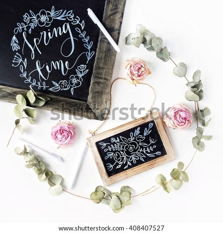 "Phrase ""spring time"" written with chalk in calligraphy style on black chalkboard with pink roses, green leaves and pen. Isolated on white. Overhead view. Flat lay, top view - stock photo"
