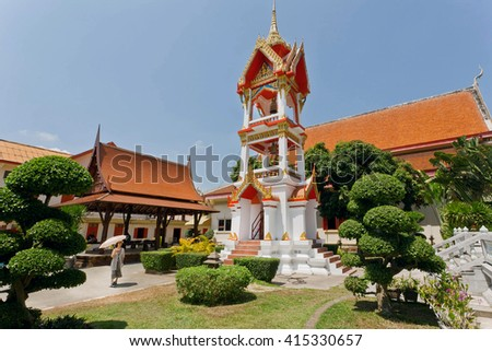 PHUKET, THAILAND - FEB 6: Woman standing past old bell tower of historical Wat Chalong temple on February 6, 2016. First written mention about the buddhist monastery belongs to 1837 - stock photo