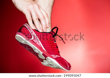 Physical running injury and leg ankle pain, sport shoes and hand massage over red background - stock photo