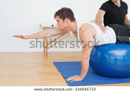 Physical therapist assisting young man with yoga ball in the gym at hospital - stock photo
