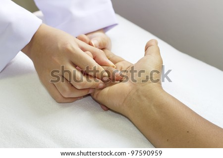 physical therapist checks range of motion for finger and hand - stock photo