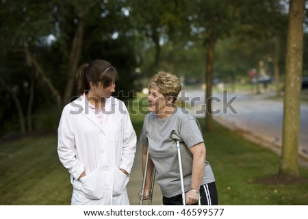 Physical therapist interacts with a patient - stock photo