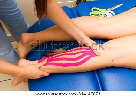Physical therapist massages injured calf with kinesiotaping - stock photo