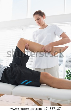 Physical therapist massaging leg of man at health spa - stock photo