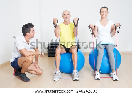 Physical therapist showing skipping rope exercise to a couple of seniors - stock photo