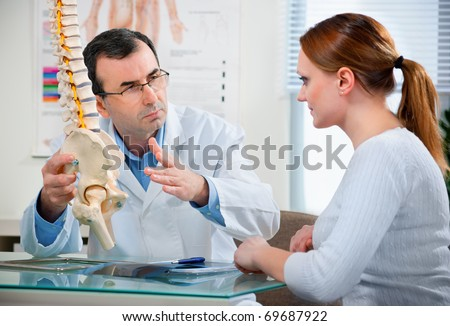 Physical Therapist shows the problem areas on the model of the spine to patient and explains the cause of her pain. - stock photo