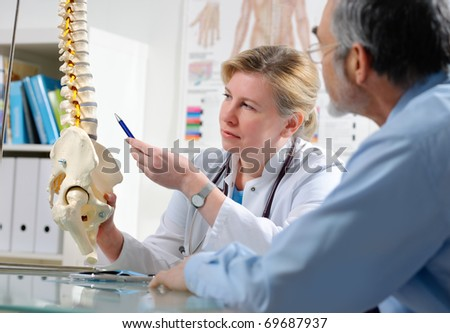 Physical Therapist shows the problem areas on the model of the spine to patient and explains the cause of his pain. - stock photo