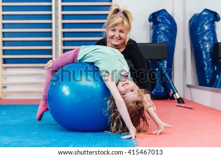 Physical therapist working with cute preschooler little girl in gymnasium, stretching over fitness ball - stock photo