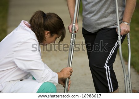 physical therapists adjusts a patient's crutches - stock photo