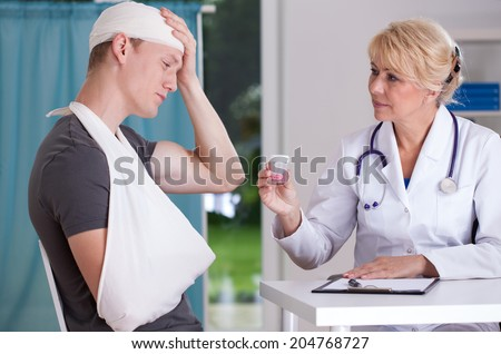 Physician giving to patient pills for headache - stock photo