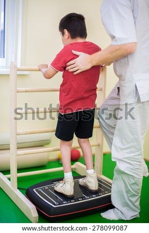 physician supports a child standing on the training platform - stock photo