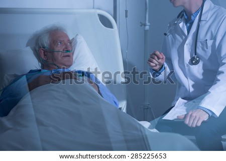 Physician talking with sick elderly man about treatment - stock photo