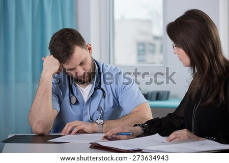 Physician who commit medical error talking with lawyer - stock photo
