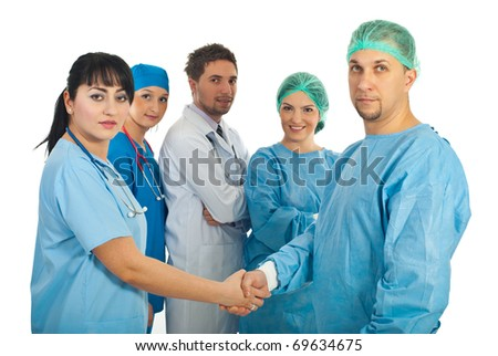Physician woman and surgeon man handshake and their team of doctors standing with hands crossed in the middle of them isolated on white background - stock photo