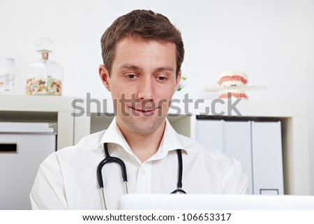 Physician working with his laptop in the doctor's office - stock photo