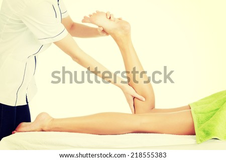 Physio therapist trying to fix the legs over white background - stock photo
