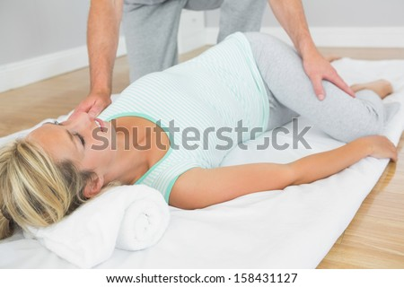 Physiotherapist checking patients hips on a mat on the floor in bright room - stock photo