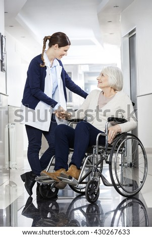Physiotherapist Consoling Senior Patient In Wheelchair - stock photo