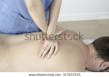 Physiotherapist doing a Dog technique over back spine. Osteopathy. - stock photo