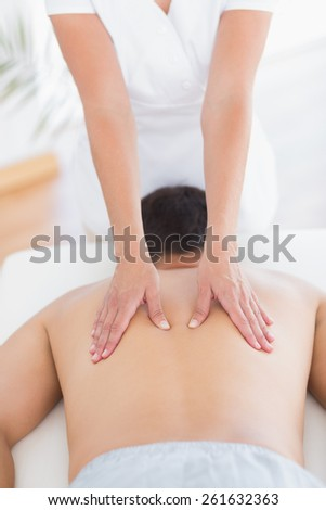 Physiotherapist doing back massage to her patient in medical office - stock photo