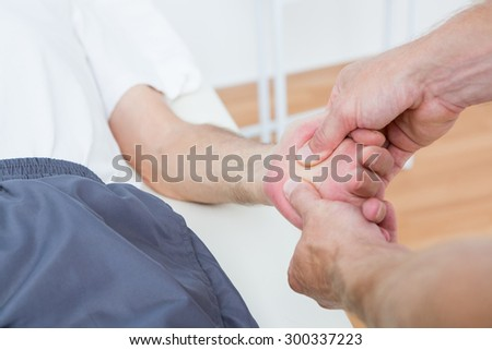 Physiotherapist doing hand massage in medical office - stock photo
