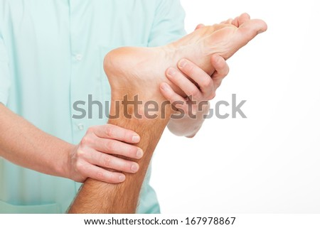 Physiotherapist doing medical massage of injured man's foot - stock photo