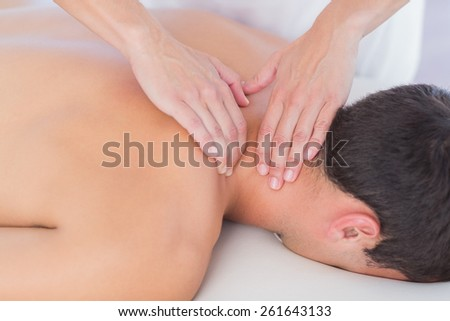 Physiotherapist doing neck massage to her patient in medical office - stock photo