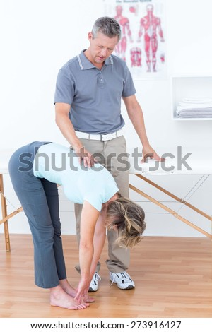 Physiotherapist examining his patient back in medical office - stock photo