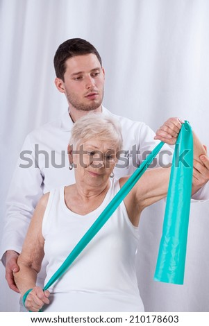 Physiotherapist exercising with elderly patient with elastic band  - stock photo
