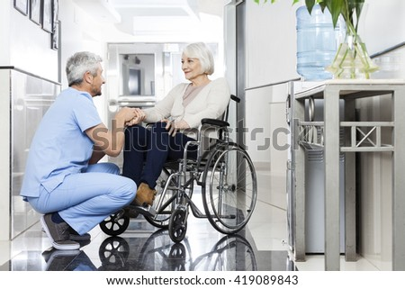 Physiotherapist Holding Senior Patient's Hand On Wheelchair - stock photo