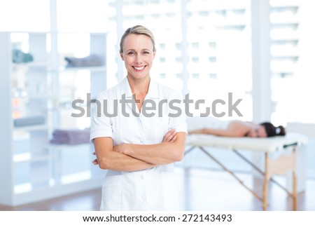 Physiotherapist smiling at camera arms crossed in medical office - stock photo