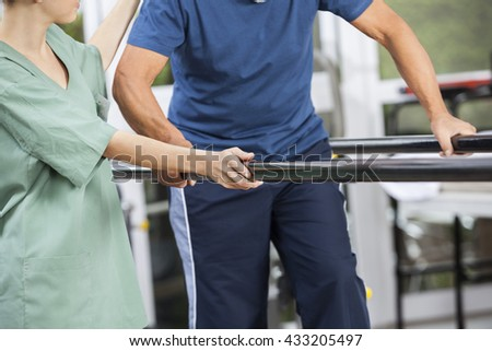 Physiotherapist Standing By Senior Man Walking Between Parallel  - stock photo