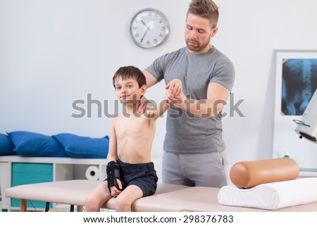 Physiotherapist training with little patient after injury - stock photo