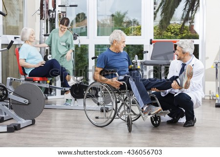 Physiotherapists Guiding Patients To Exercise At Rehab Fitness C - stock photo
